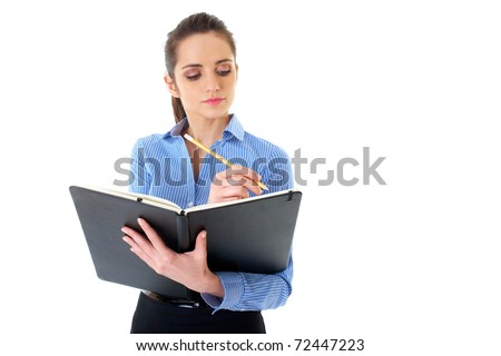 young happy female in blue shirt makes some notes in notepad, isolated on white - stock photo