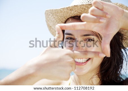 young happy female looking through a frame made from her fingers - stock photo
