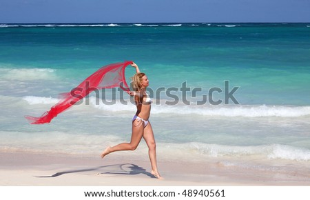 Young  happy female running with red sheer on tropical beach - stock photo