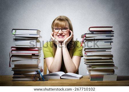 young happy female student with glasses and lots of books at a table - stock photo