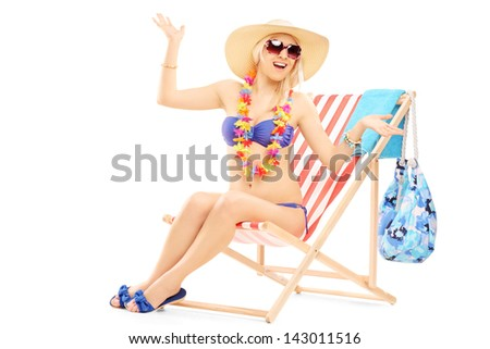 Young happy female with a hat posing on a beach chair isolated on white background - stock photo
