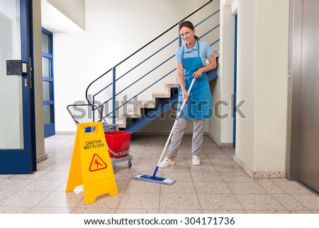 Young Happy Female Worker With Cleaning Equipments And Wet Floor Sign On Floor - stock photo