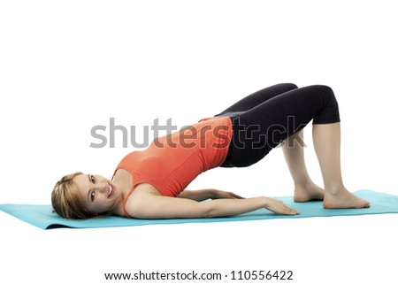 young happy fitness woman exercising on a blue mat on white background - stock photo