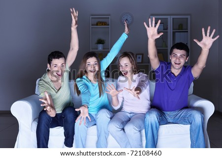 Young happy friends are watching TV at home - stock photo