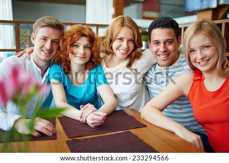 Young happy friends sitting at table - stock photo