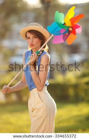 Young happy funny (vintage) dressed woman close-up ,making funny face and holding  colorful weather vane,looking like flower