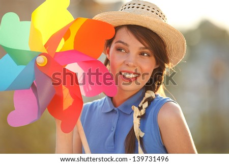Young happy funny (vintage) dressed woman close-up  with colorful weather vane,looking like flower  Picture ideal for illustating woman magazines. - stock photo
