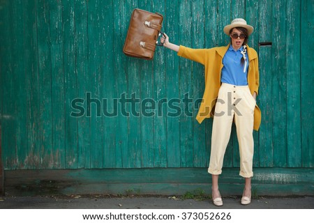 Young happy funny (vintage) dressed woman waves retro suitcase. Old green fence on the background.