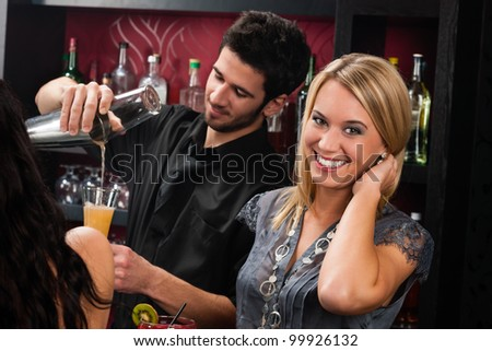 Young happy girl at cocktail bar bartender mixing drink