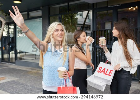 young happy girl calling for taxi cab along city sidewalk with coffee cup sale shopping bag friends - stock photo