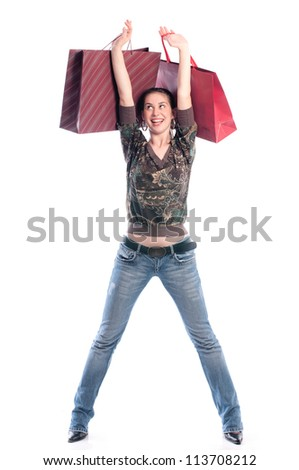Young happy girl holding and rise up bags on white, not isolated - stock photo