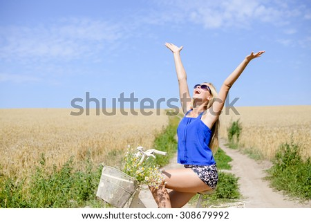 Young happy girl in blue belly shirt and shorts sitting on bicycle lifting her arms with joy riding along earth road in field of wheat, on sunny day outdoors background - stock photo
