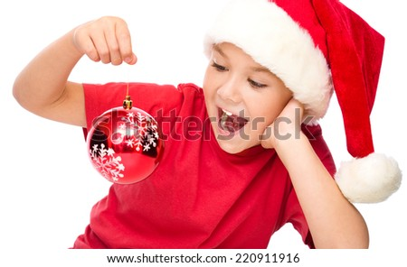 Young happy girl in santa hat is holding a christmas decoration, isolated over white - stock photo