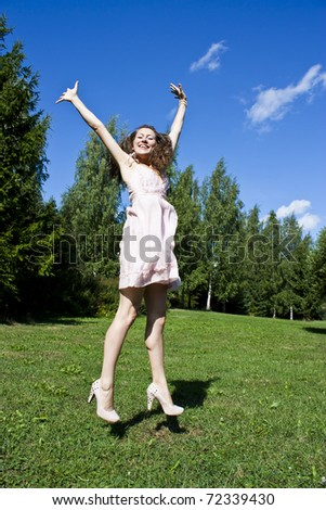 Young happy girl jumps in the street in the summer. Hands up