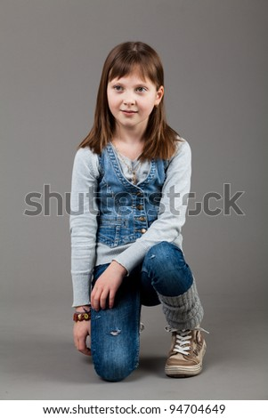 young happy girl.  little girl on a gray background - stock photo