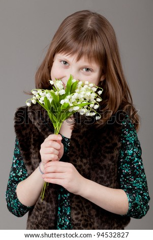 young happy girl.  little girl on a gray background. Girl with flowers lily of the valley. - stock photo