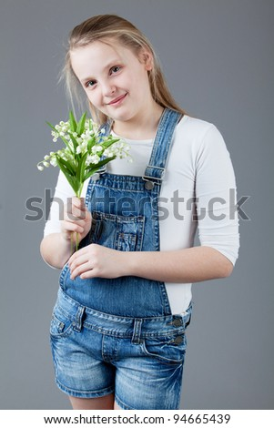 young happy girl.  little girl on a gray background. portrait of a beautiful little girl with flowers. - stock photo