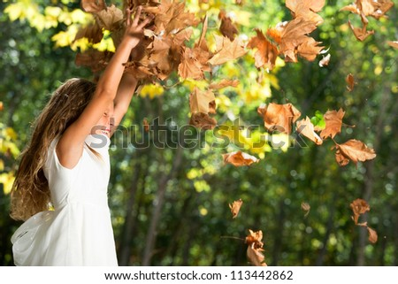 Young happy girl playing with autumn leaves in park.