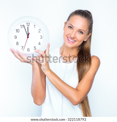 young happy girl posing in studio and holding white clock isolated on white background.