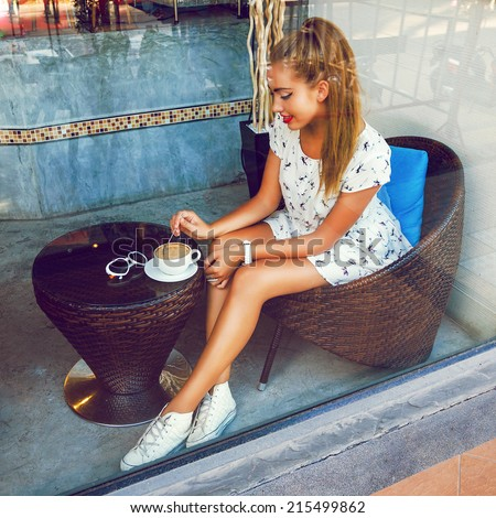 Young happy girl sitting alone at cafeteria and enjoy her morning coffee, wearing cute retro dress and sneakers, have blond long hairs at ponytail.Fashion image taken through the window of restaurant. - stock photo