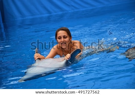 Young happy girl swimming with the dolphins