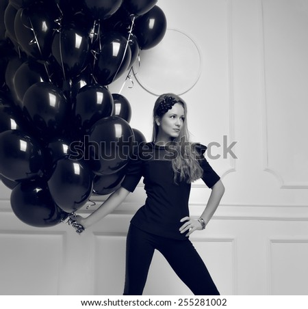 Young happy girl with black balloons as a present for birthday party smiling and looking at the corner black and white picture - stock photo
