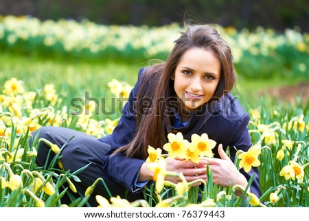 young happy girl with yellow daffodil flowers, spring concept - stock photo