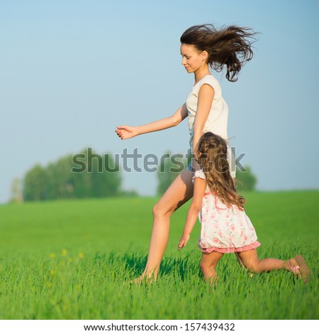 Young happy girls running down green wheat field with her friend together - stock photo