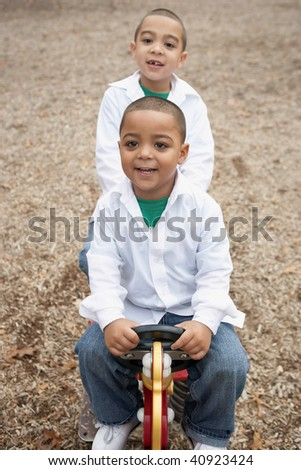 Young happy hispanic boys playing at school playground - stock photo