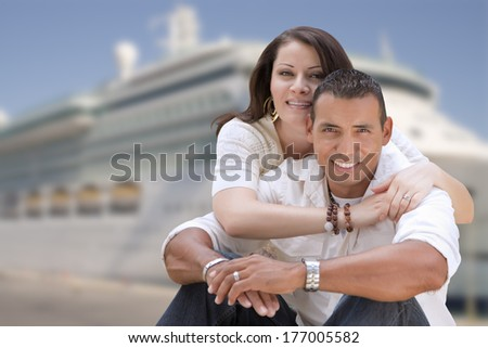 Young Happy Hispanic Couple Hugging On The Dock In Front of a Cruise Ship. - stock photo