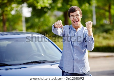 Young happy hispanic man wearing glasses holding out car keys and celebrating win with raised fist and scream against blue car outdoors - new drivers concept - stock photo
