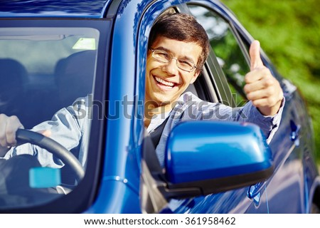 Young happy hispanic man wearing glasses sitting inside car, holding steering wheel,  showing thumb up hand gesture through car window and laughing - new drivers concept - stock photo