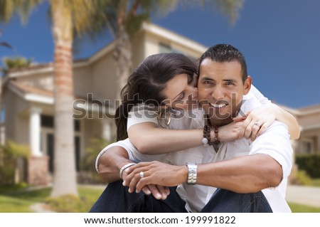 Young Happy Hispanic Young Couple in Front of Their New Home.