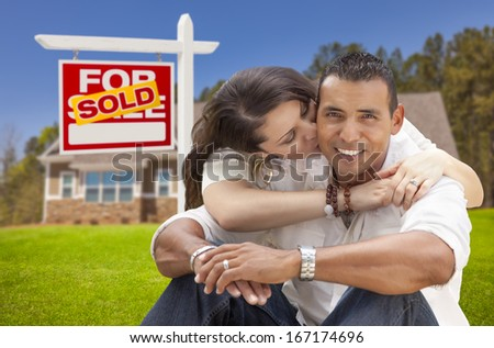 Young Happy Hispanic Young Couple in Front of Their New Home and Sold For Sale Real Estate Sign. - stock photo