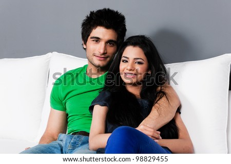 young happy indian couple relaxing on the sofa, happy multi ethnic couple relaxing on white sofa
