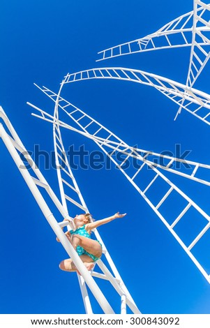 young happy kid - girl - climbing white ladders going nowhere up on natural sky background, outdoor - stock photo