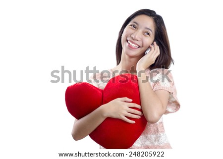Young happy lady with heart shaped pillow calling on a cellphone. Valentines' Day concept. - stock photo
