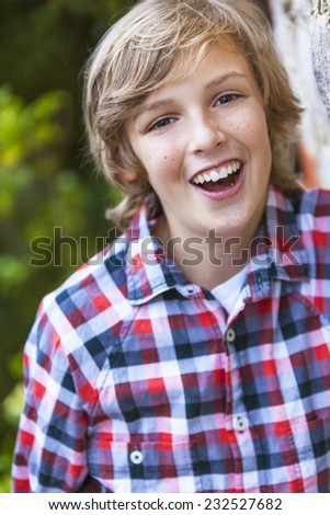 Young happy laughing boy outside wearing a checked plaid shirt - stock photo