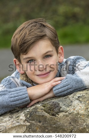 Young happy laughing male boy blond child outside leaning on his hands in autumn fall sunshine