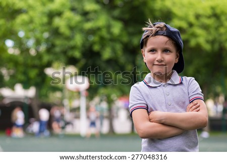 Young happy little boy smiling greeting someone in the park - stock photo