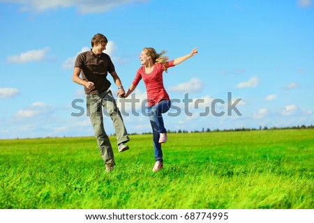 Young happy lovers running on meadow with green grass and blue sky