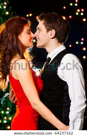 Young happy loving couple dancing at Christmas celebration near New Year's tree - stock photo