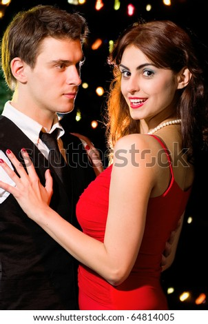 Young happy loving couple dancing at Christmas (or Valentine's day) celebration - stock photo