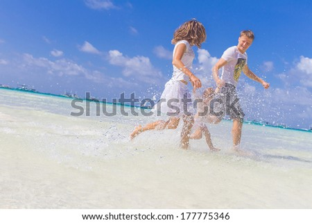 young happy loving family with baby girl on tropical sea and beach background - stock photo