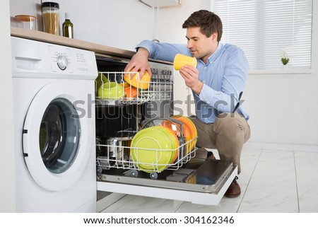 Young Happy Man Arranging Dishes In Dishwasher In Modern Kitchen - stock photo