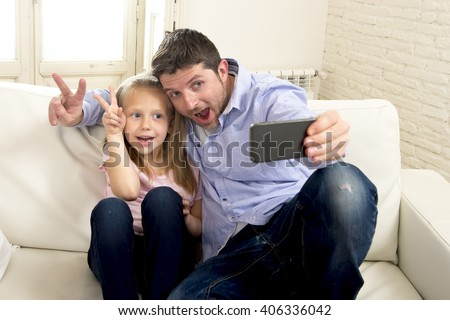 young happy man having fun with his little cute blond daughter taking selfie photo with mobile phone enjoying together at home sofa couch in father and little girl self portrait picture concept - stock photo