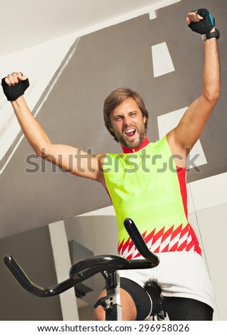 Young happy man in a jim spinning a cycle, victory sign- arms up, smiling excited.  - stock photo