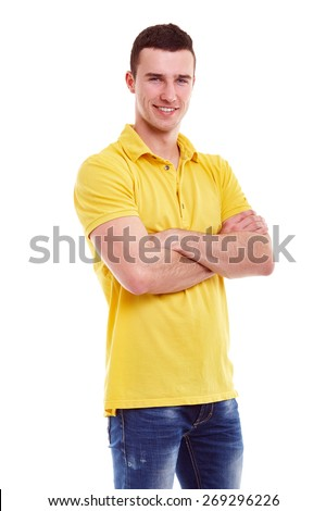 Young happy man in a yellow polo shirt with crossed arms - stock photo