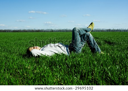 young happy man lying on the green field - stock photo
