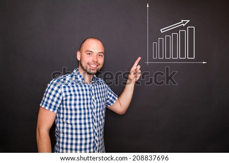 Young happy man pointing  his finger to the graph